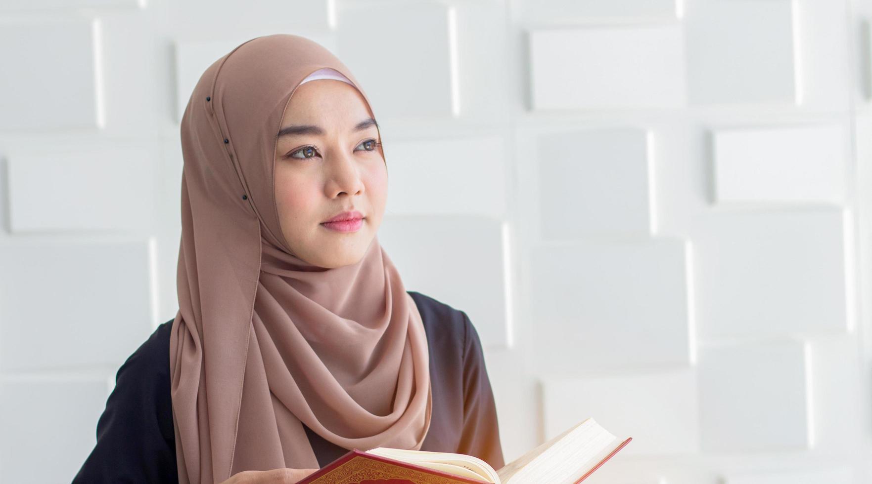 giovane donna musulmana vestita con un hijab nero, pregando per Allah, copia dello spazio. concetto rituali religiosi per la pace foto