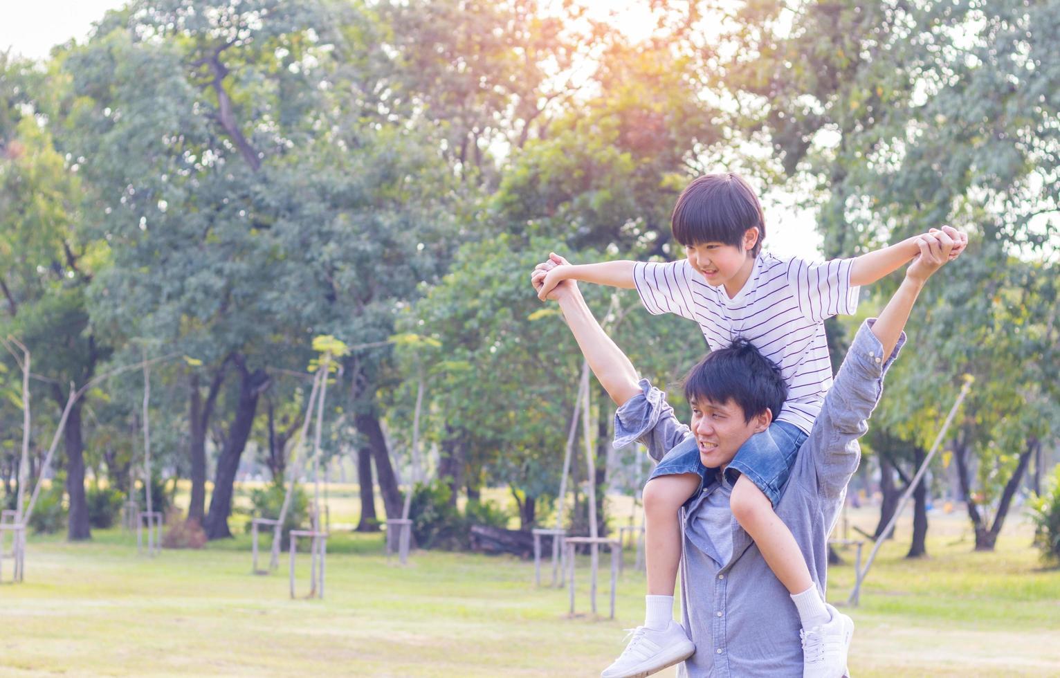 padre e figlio carino che giocano aeroplano di carta nel parco. il figlio è sulla schiena di suo padre foto