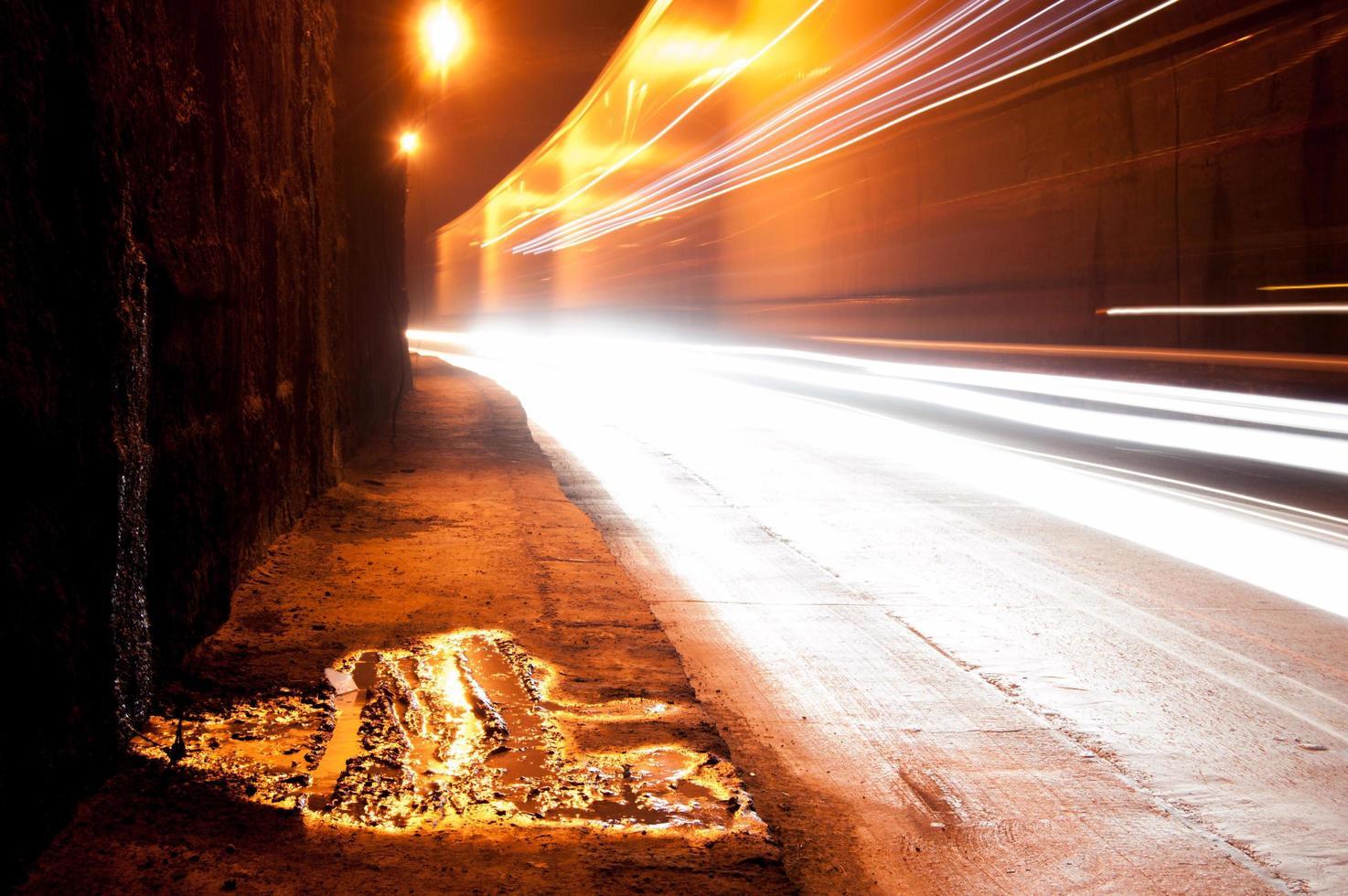 un tunnel buio con scie luminose foto