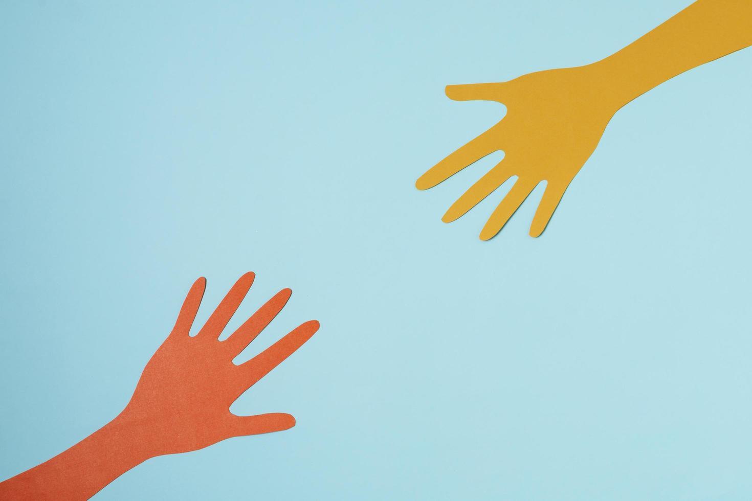 mani di carta su sfondo blu foto