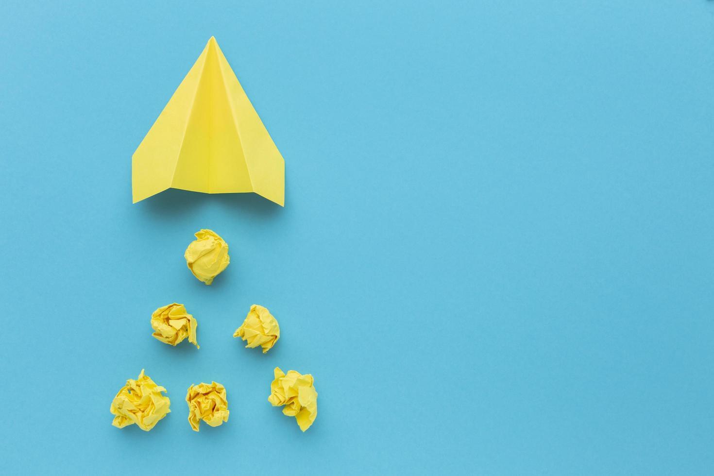 carta gialla stropicciata con aeroplano di carta foto