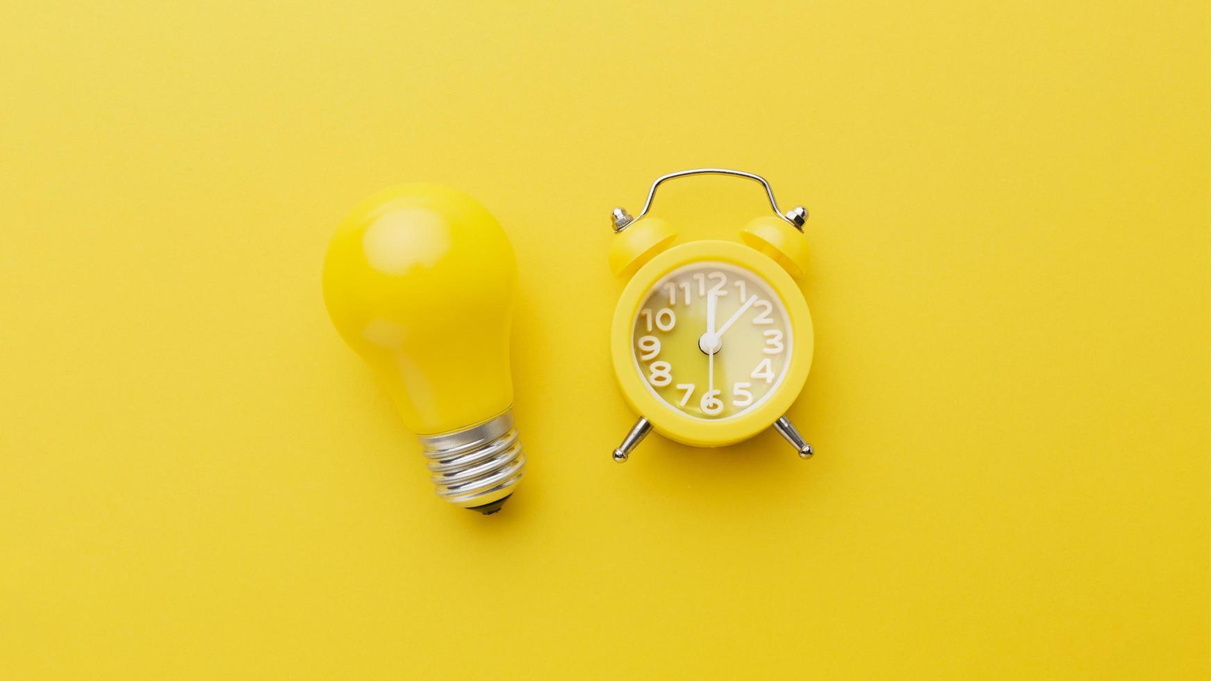 lampadina gialla e sveglia foto