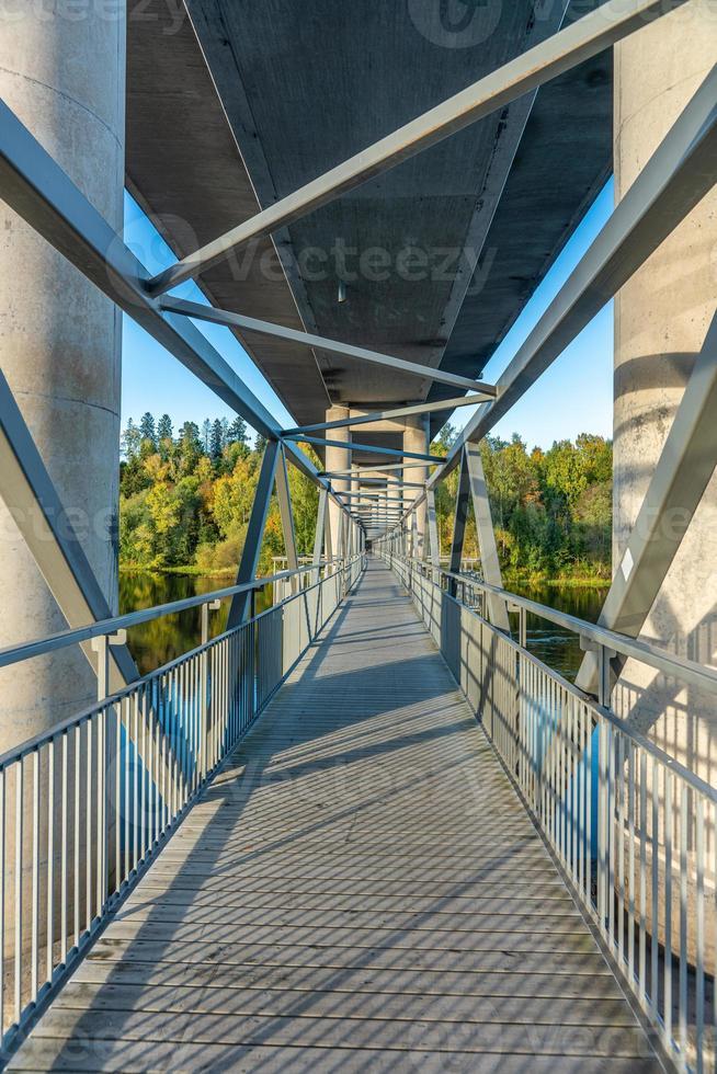 passerella sotto un grande ponte che attraversa un fiume foto