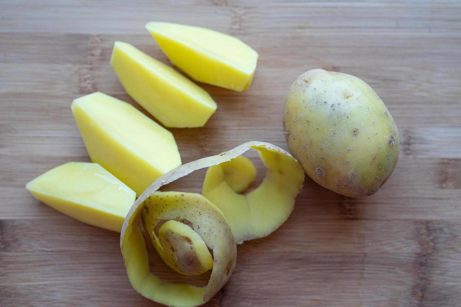 patate crude con la buccia su un tagliere foto