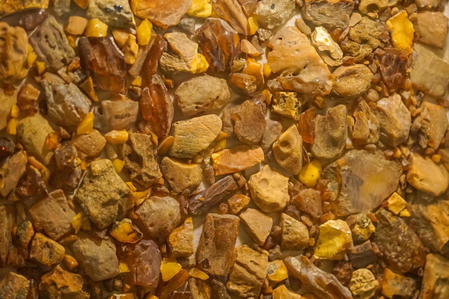 sullo sfondo la grande ambra naturale di diverse sfumature di giallo e arancio foto
