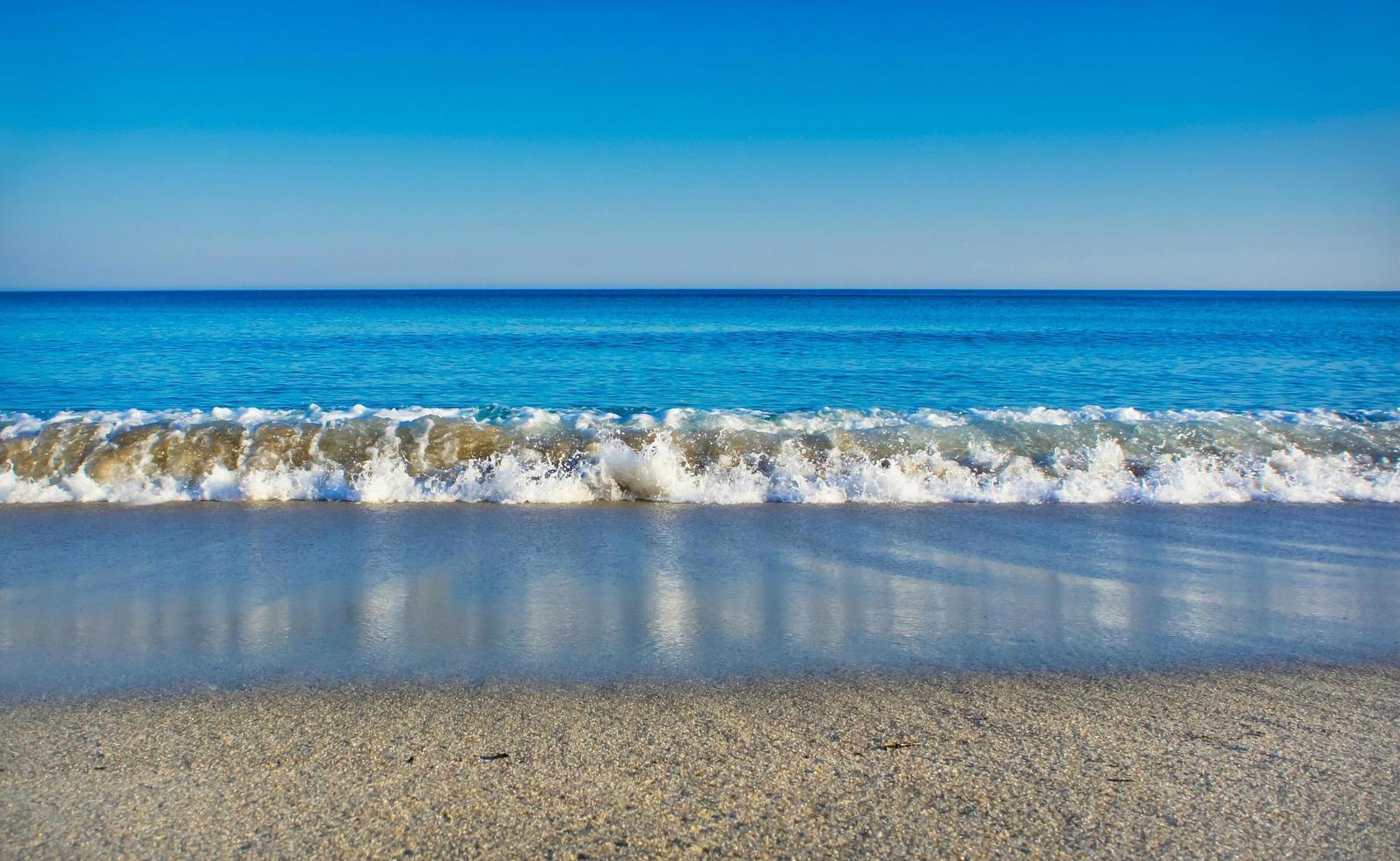 vista sul mare con un mare cristallino, cielo senza nuvole e spiaggia di sabbia bianca foto