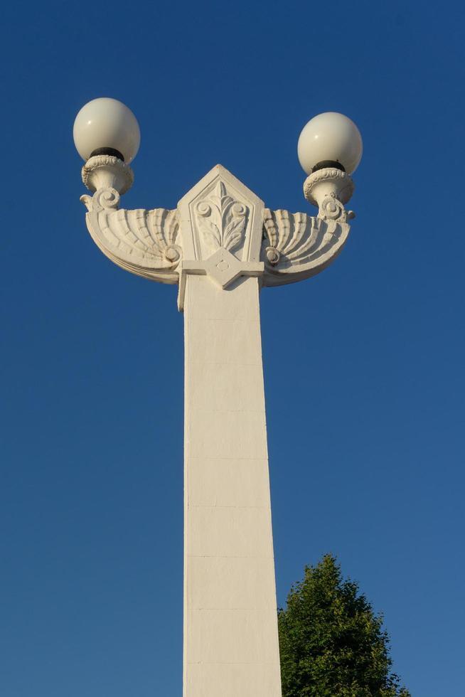 bellissimo lampione in pietra bianca sullo sfondo del cielo blu. foto
