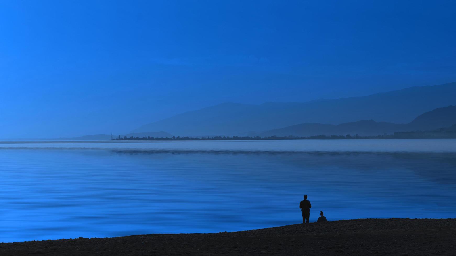 sera di vista sul mare blu e sagome di persone. foto