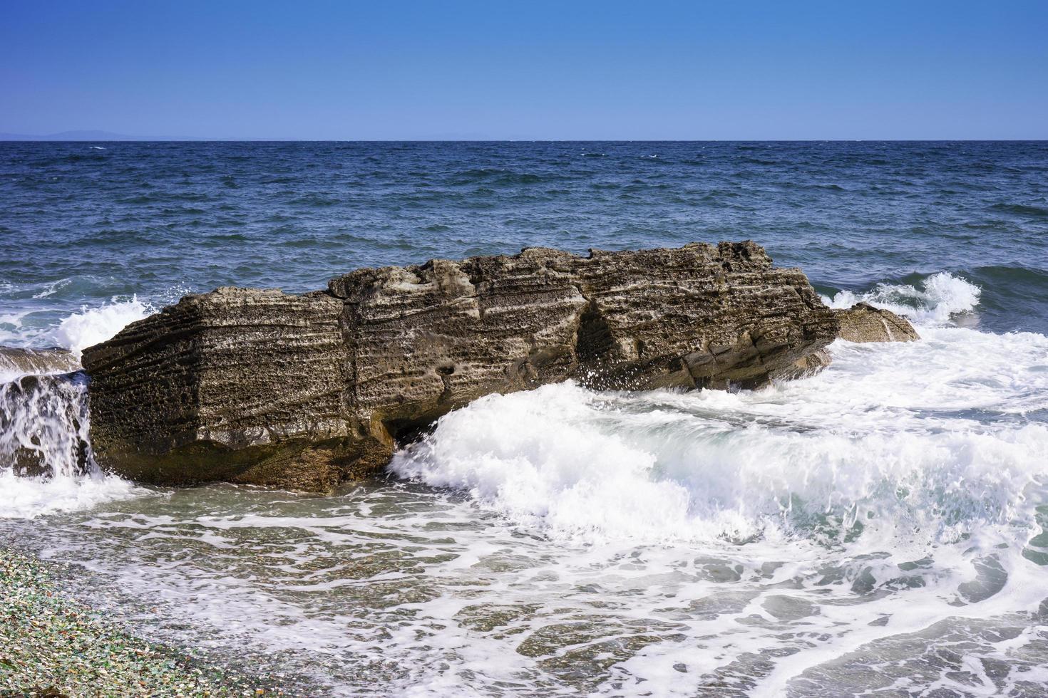 vista sul mare con una roccia tra le onde. foto