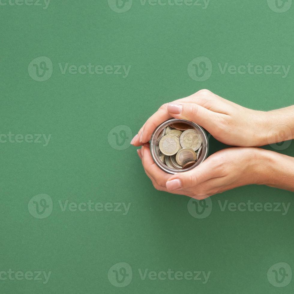 persona in possesso di vaso con monete con copia spazio su sfondo verde foto