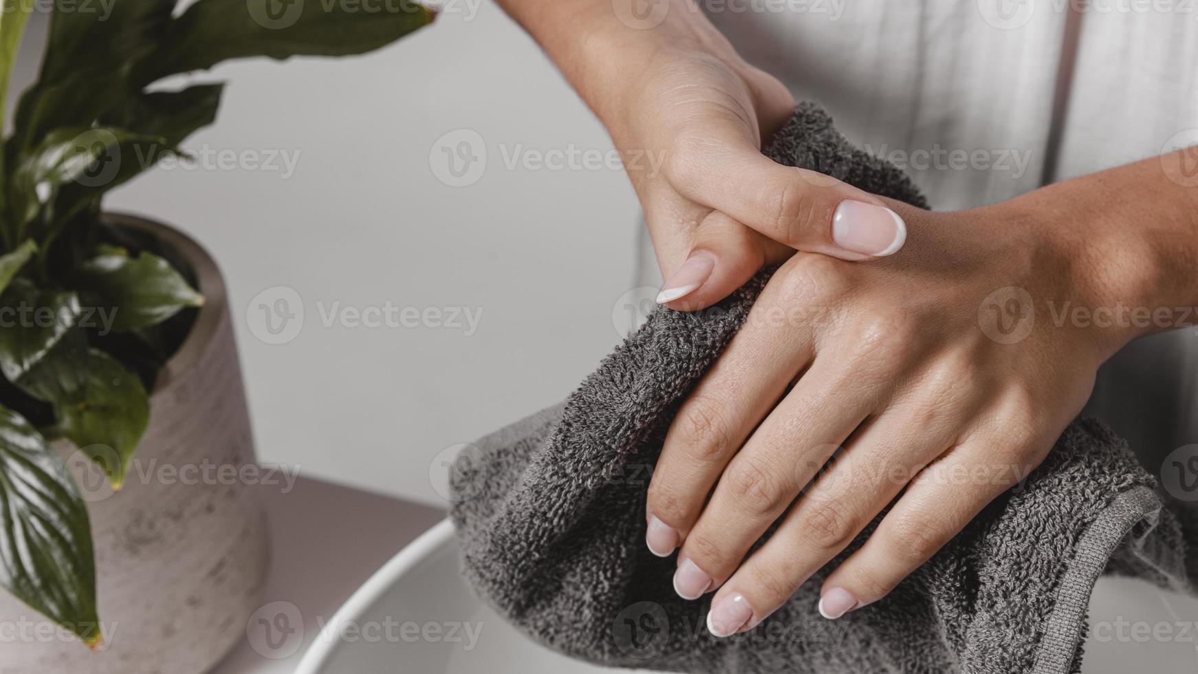 persona che si asciuga le mani con un primo piano asciugamano foto