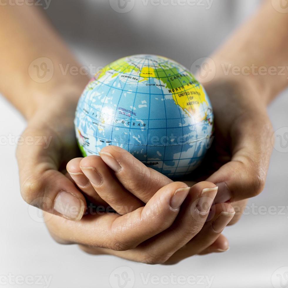 persona in possesso di un globo terrestre foto