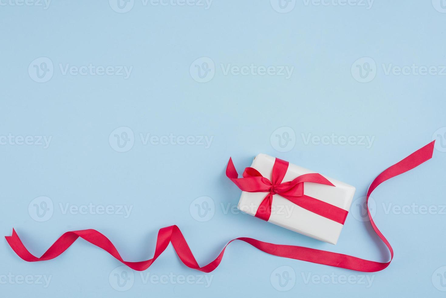 nastro rosso vicino a confezione regalo su sfondo blu foto