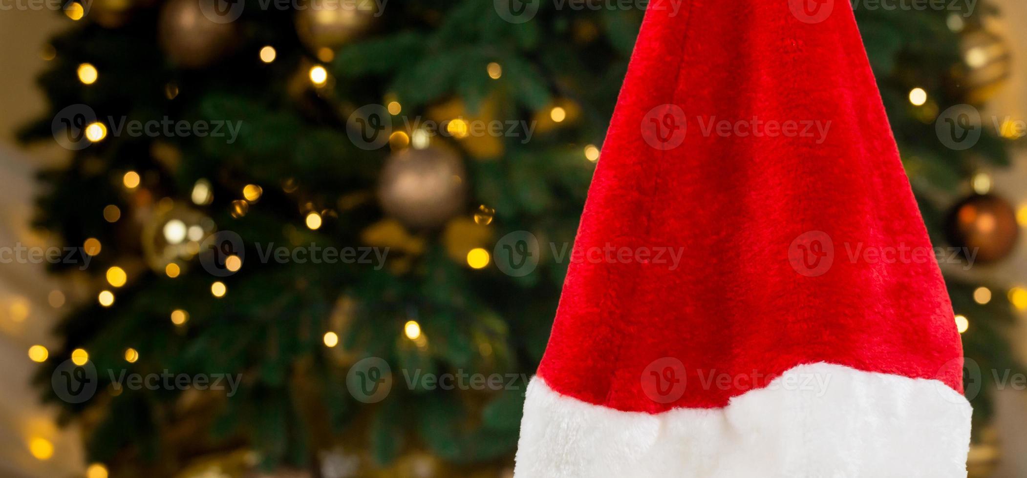 santa hat sullo sfondo di un albero di natale e ghirlande foto