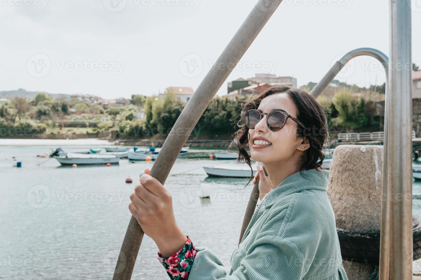 giovane donna su un molo sorridente durante una giornata di sole foto