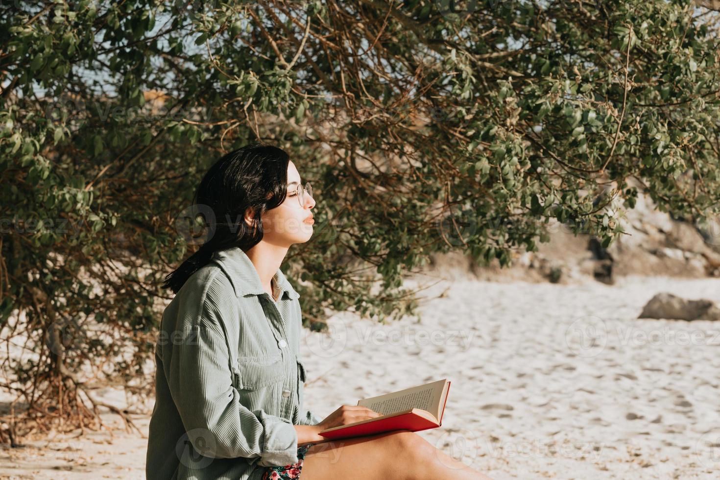 giovane donna marocchina in abiti moderni seduti sulla spiaggia leggendo un libro foto