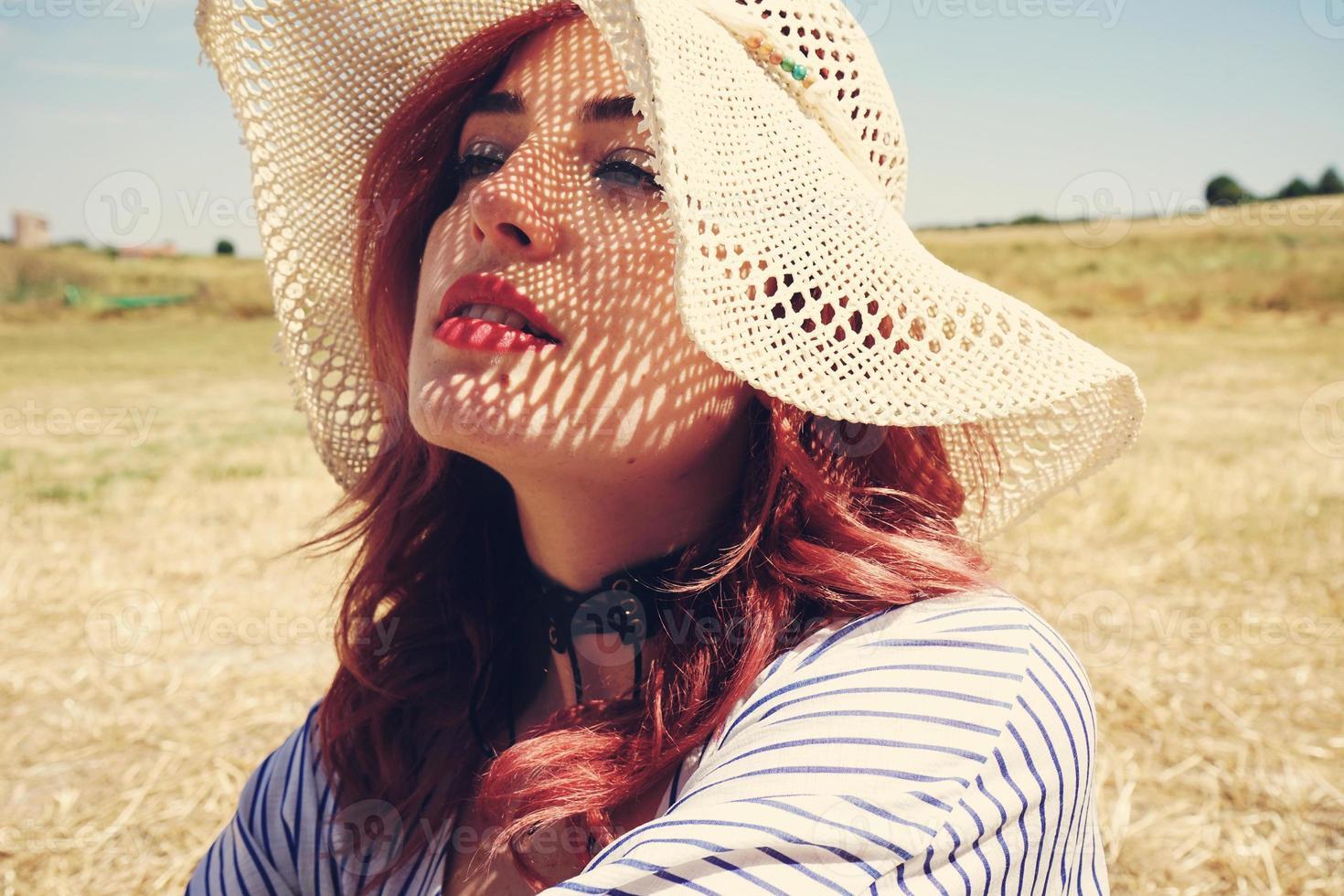 giovane donna dai capelli rossi che copre dal sole foto
