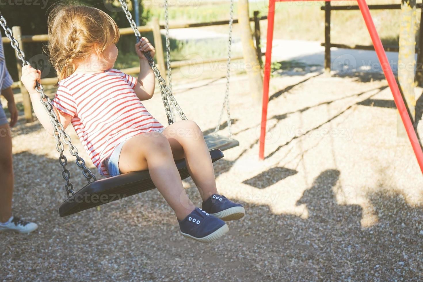 ragazza su un'altalena al parco foto