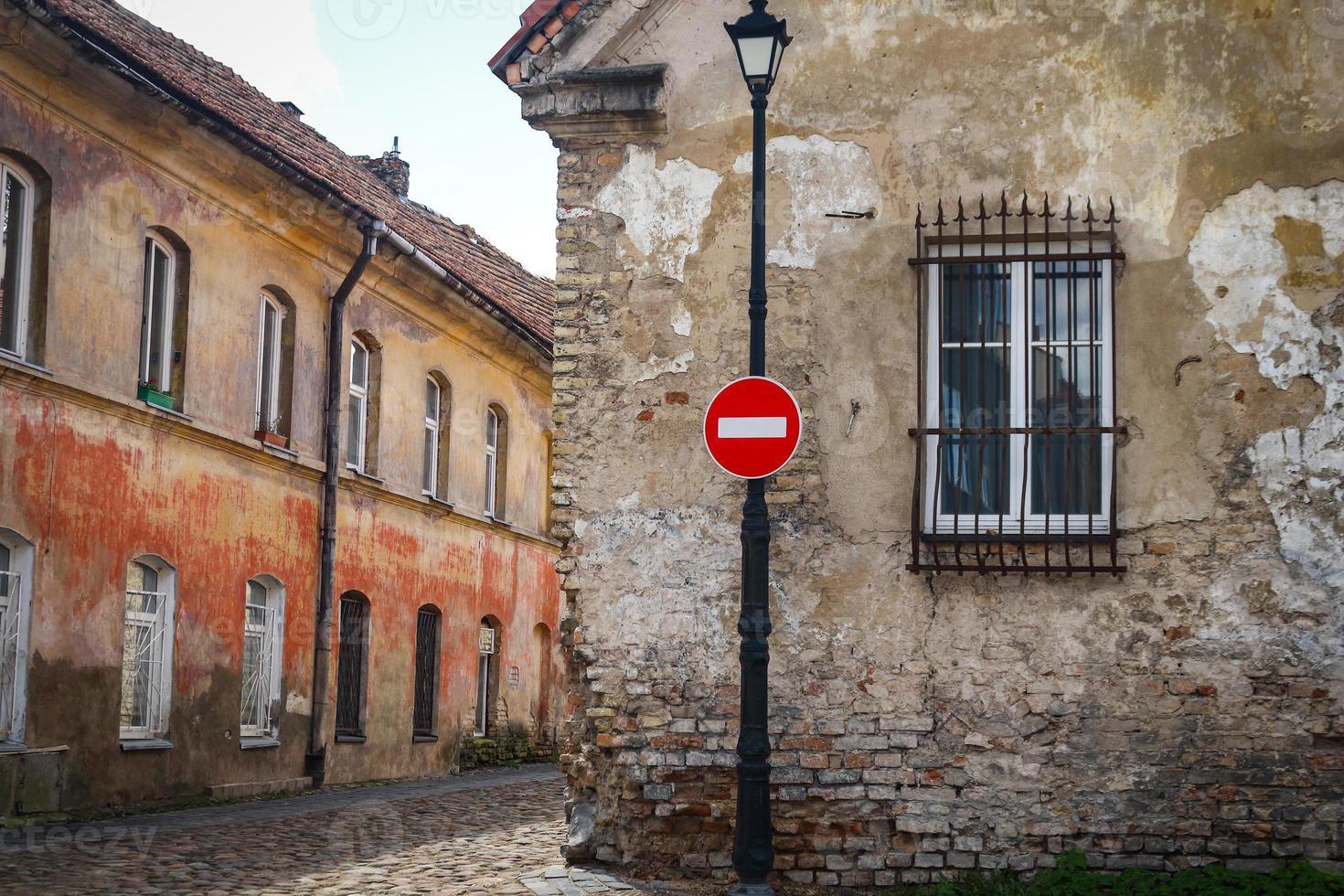 segnale di stop rosso sul lampione vicino all'edificio della città vecchia con finestra foto