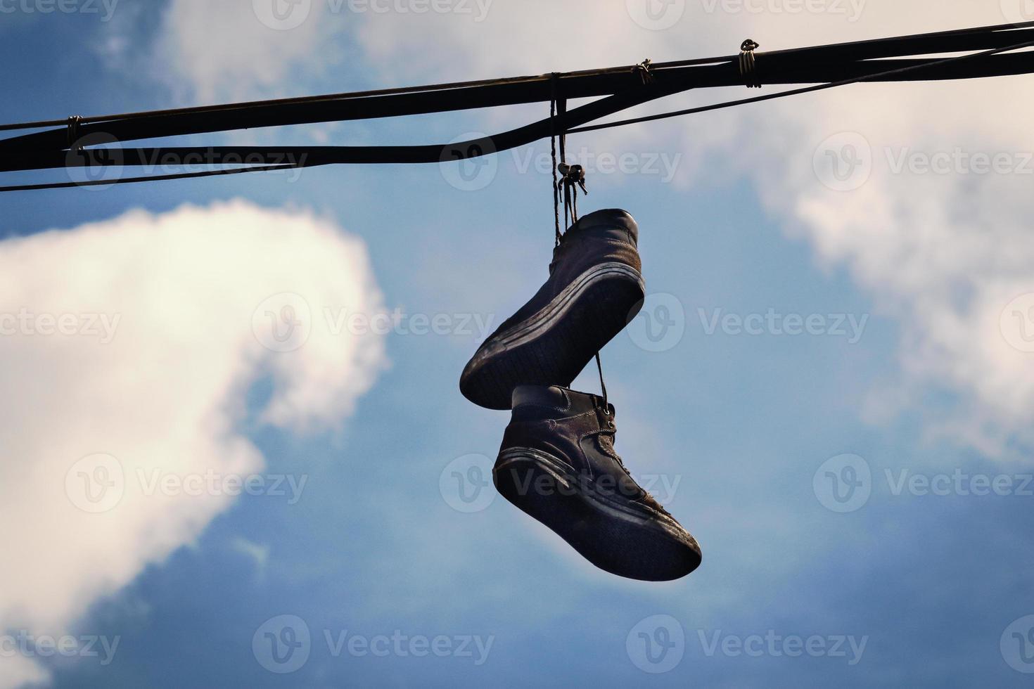 due vecchie scarpe da ginnastica sporche appese ai fili nel cielo blu con nuvole foto
