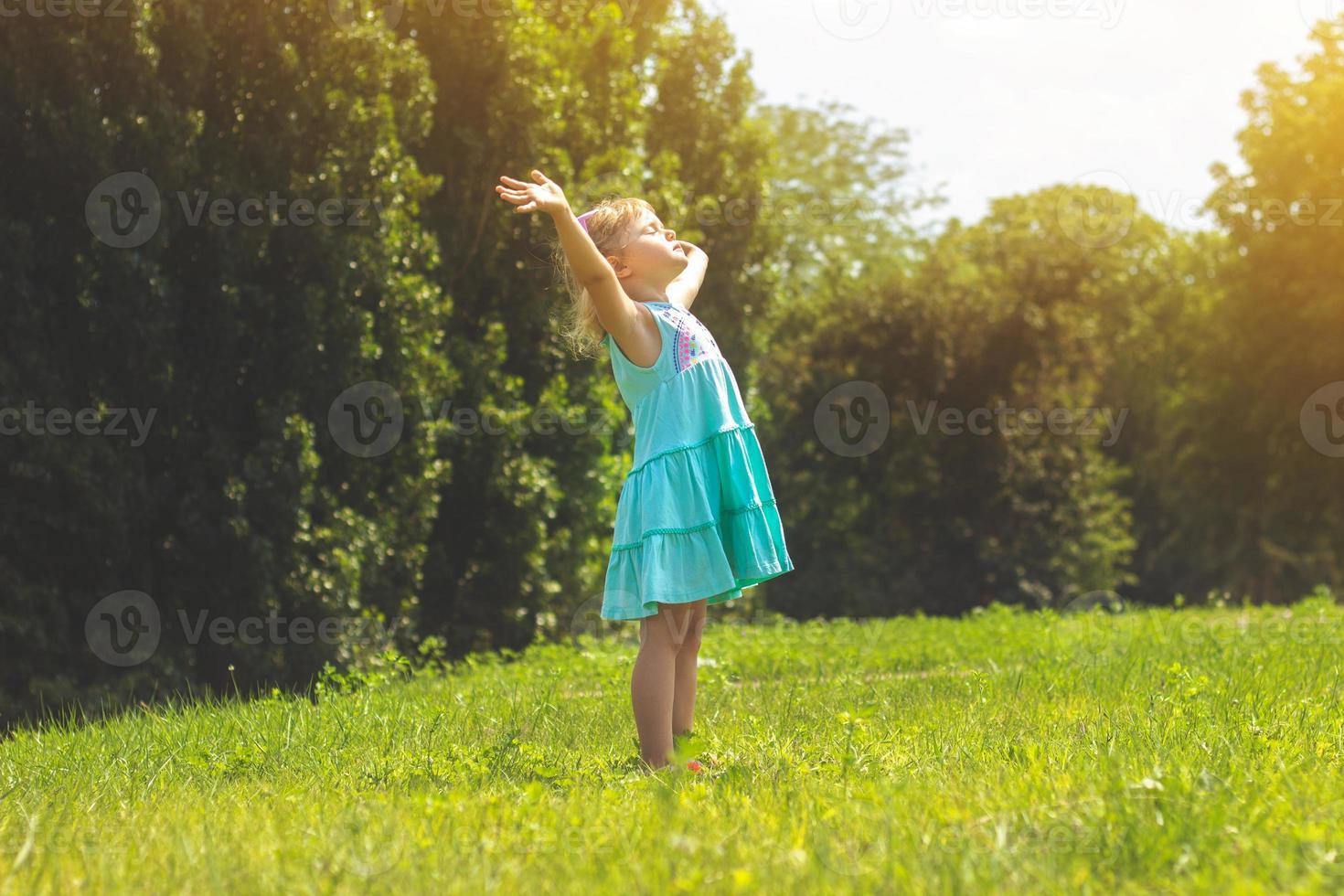 bambina nel parco con le braccia aperte concetto di vita foto