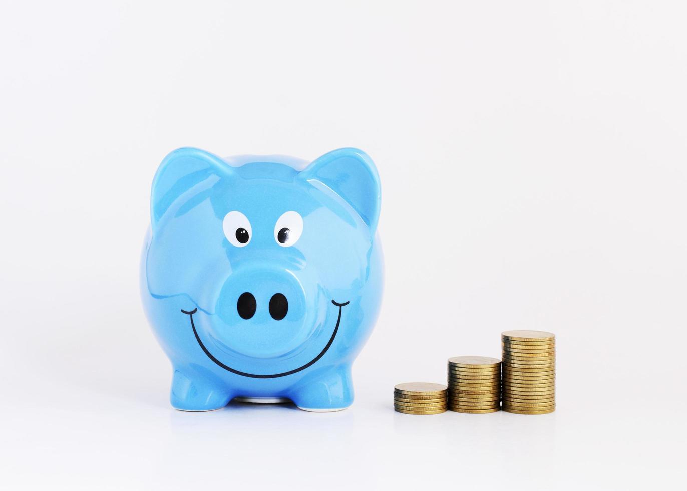 concetto di piano di risparmio con salvadanaio blu e pila di monete di denaro su sfondo bianco foto