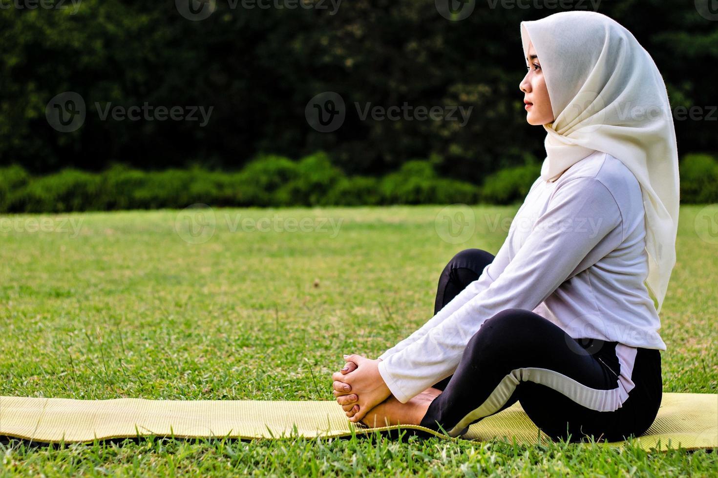 giovane donna musulmana che fa stretching muscolare prima di fare movimenti yoga foto