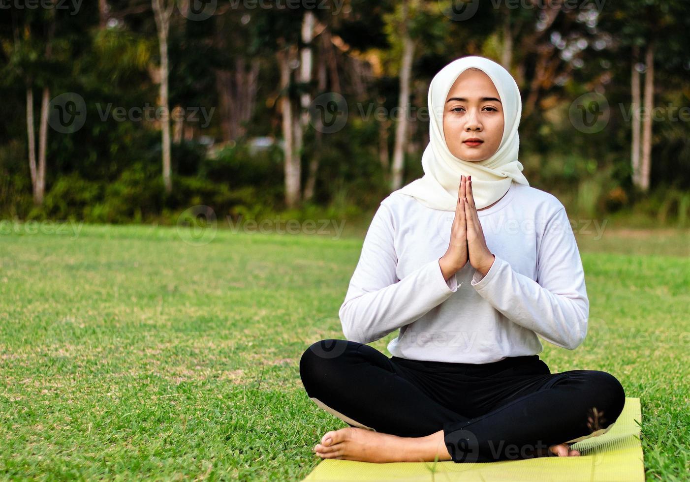 giovane donna musulmana asiatica seduta sull'erba, godendosi la meditazione foto