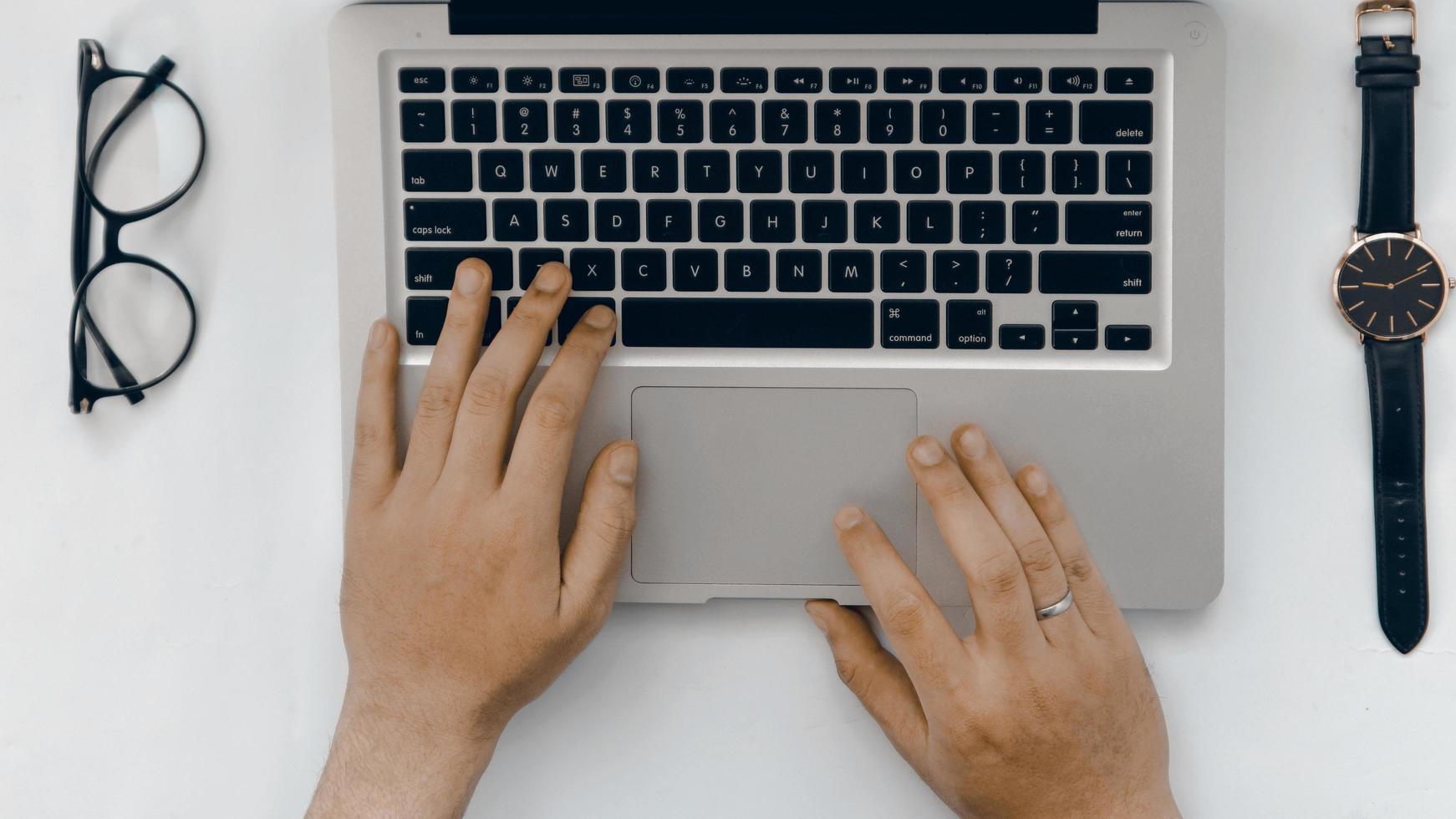 vista dall'alto mano di laptop, occhiali e orologio su sfondo bianco foto