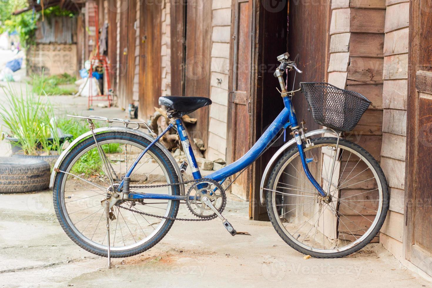 vecchia bici davanti al muro di legno di casa foto