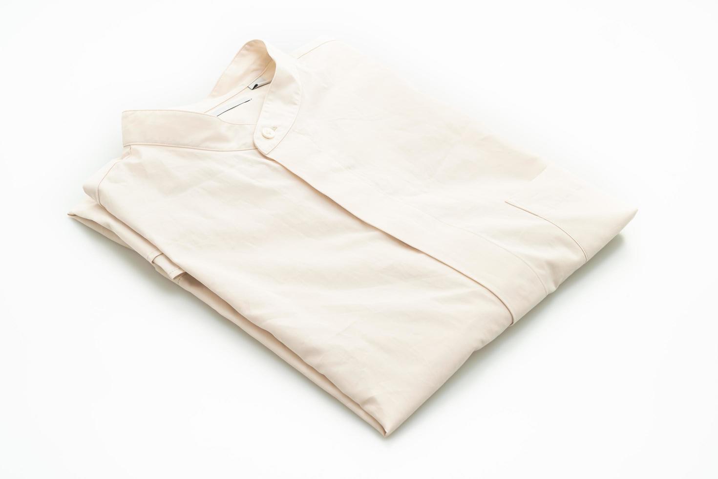 camicia beige piegata isolata su sfondo bianco foto
