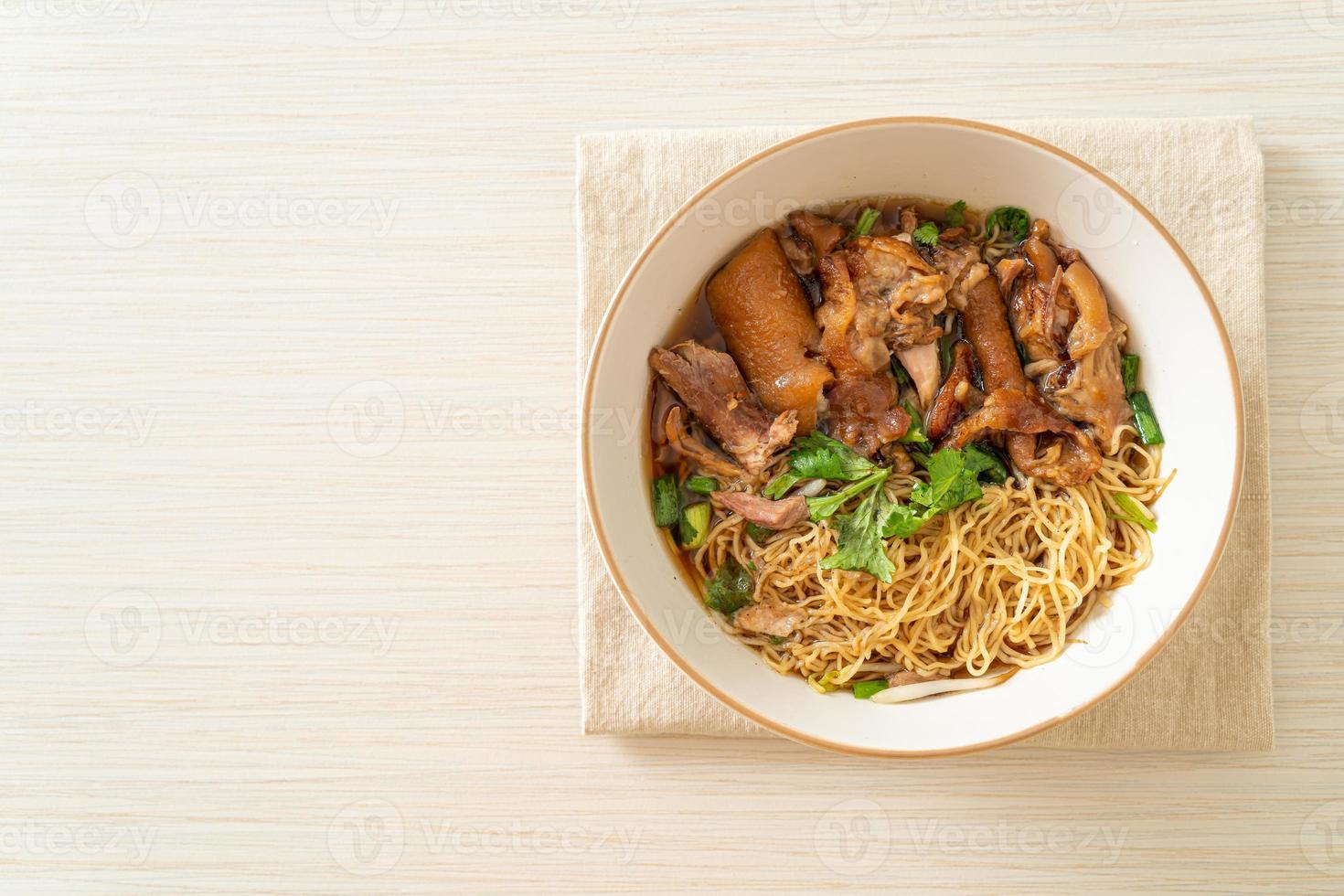 noodles di coscia di maiale in umido in zuppa marrone foto
