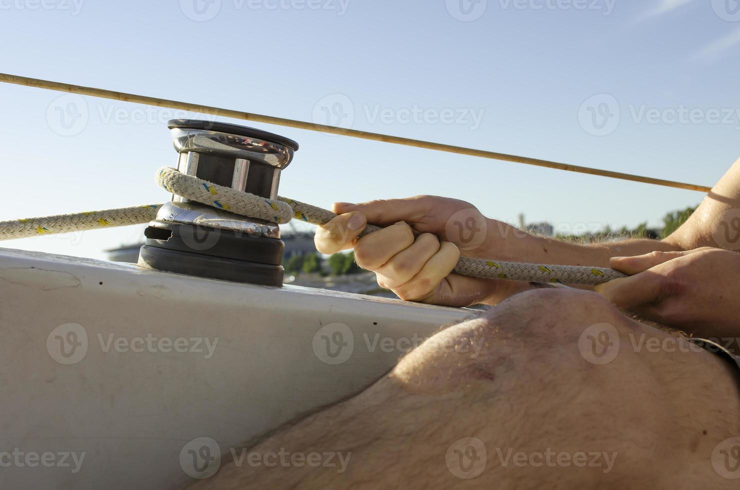 bell'uomo che lavora sulla barca a vela. sport acquatico. foto