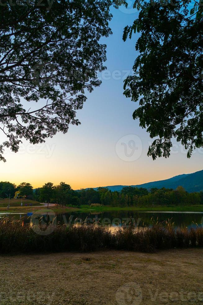 bellissimo lago a chiang mai con montagne boscose e cielo al crepuscolo in thailandia. foto