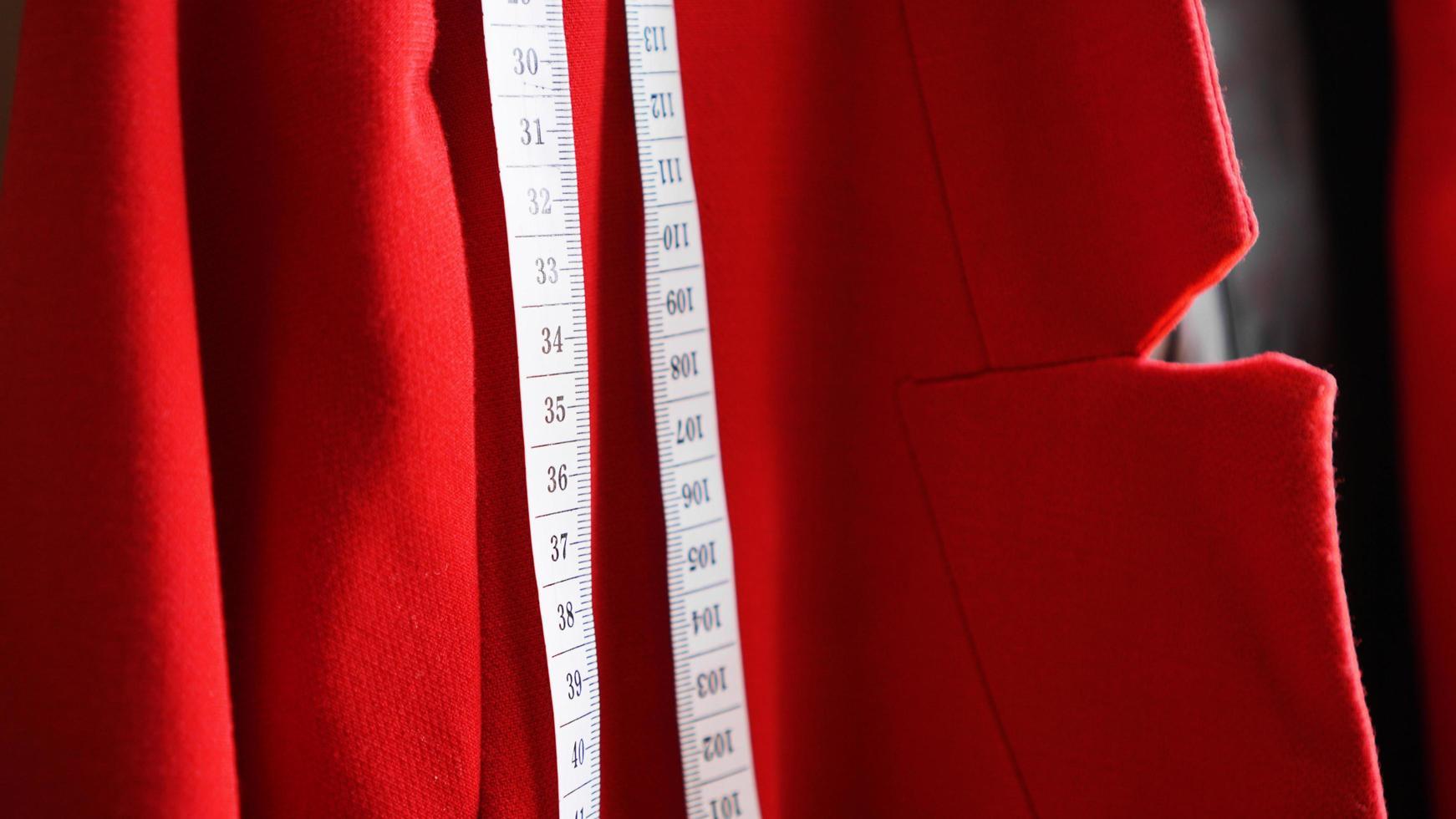 metro a nastro bianco sullo sfondo del tessuto rosso foto