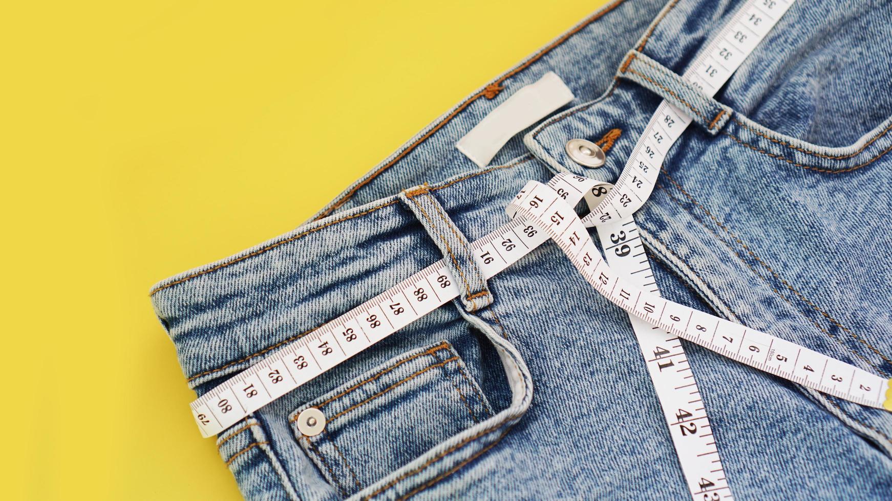 metro a nastro e jeans su uno sfondo giallo brillante foto