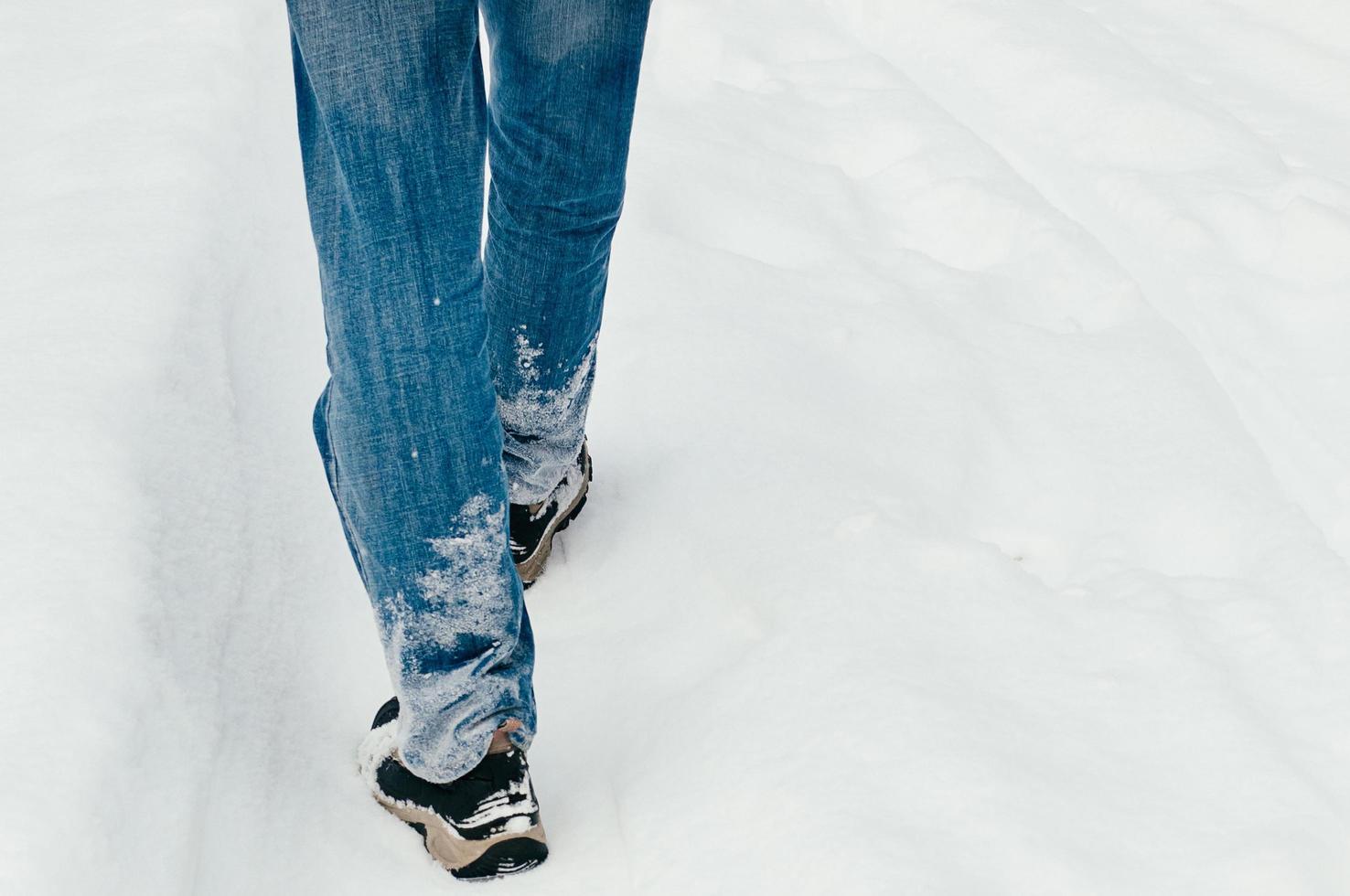 vista posteriore delle gambe maschili che camminano nella neve foto