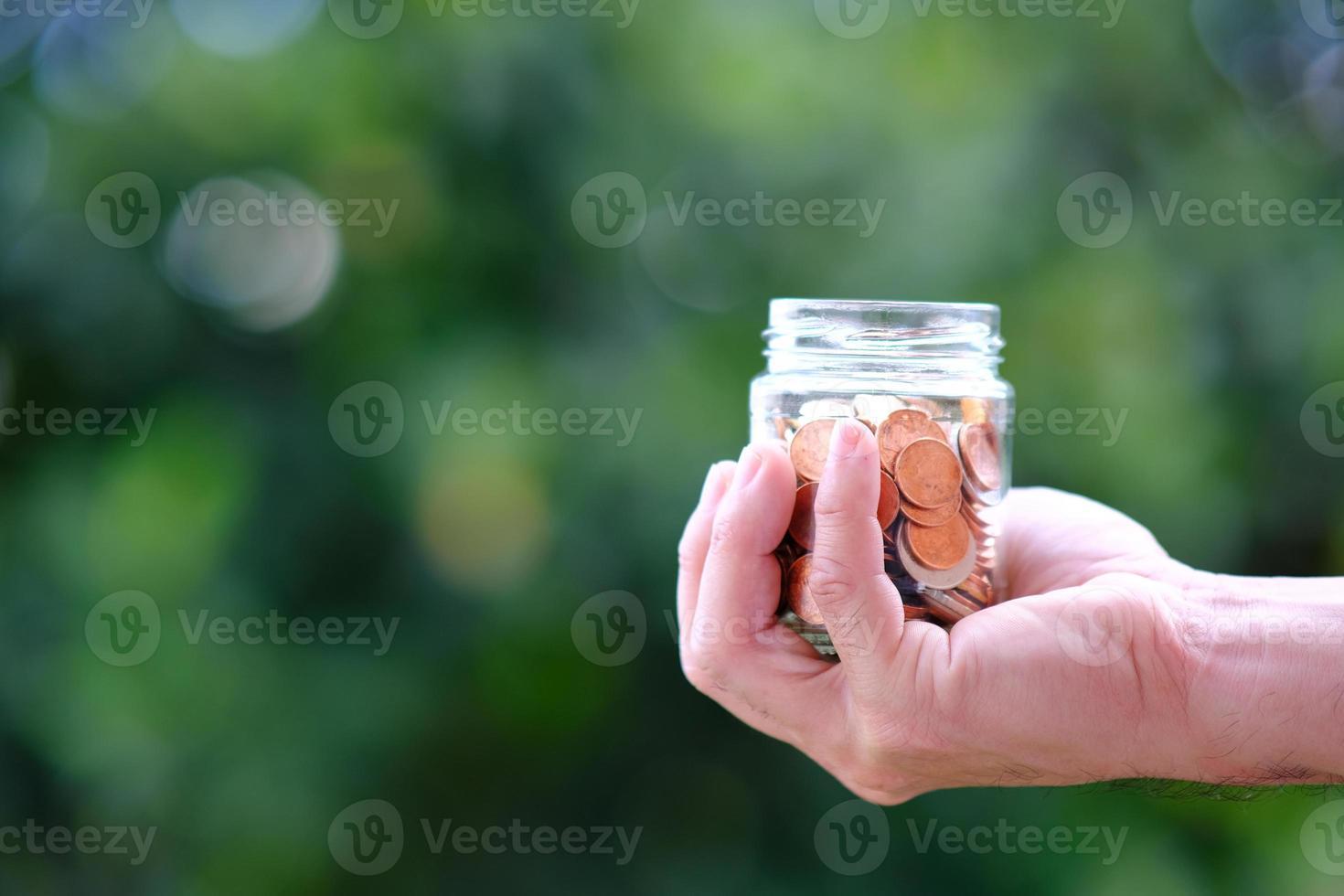 concetto di risparmio di denaro, mano che tiene la moneta in barattolo foto