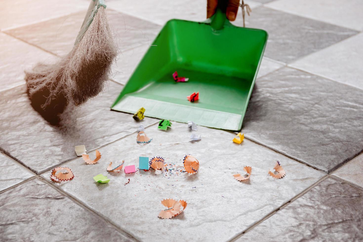 spazzare con una scopa e una paletta i ritagli di piastrelle di carta. foto