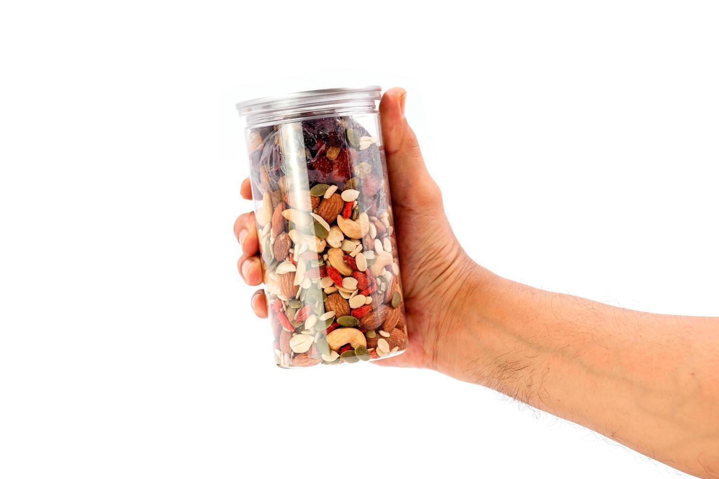 cereali integrali e bottiglia di plastica di frutta secca in mano. foto