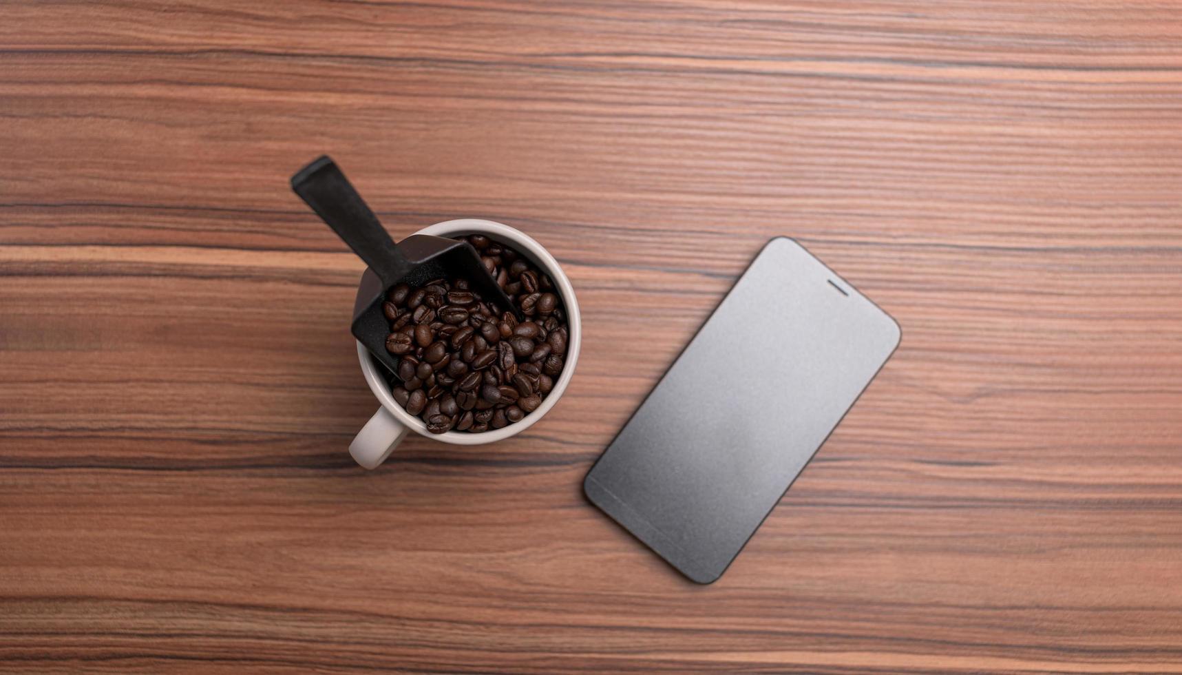 una tazza di caffè in grani e un telefono sono sulla scrivania foto