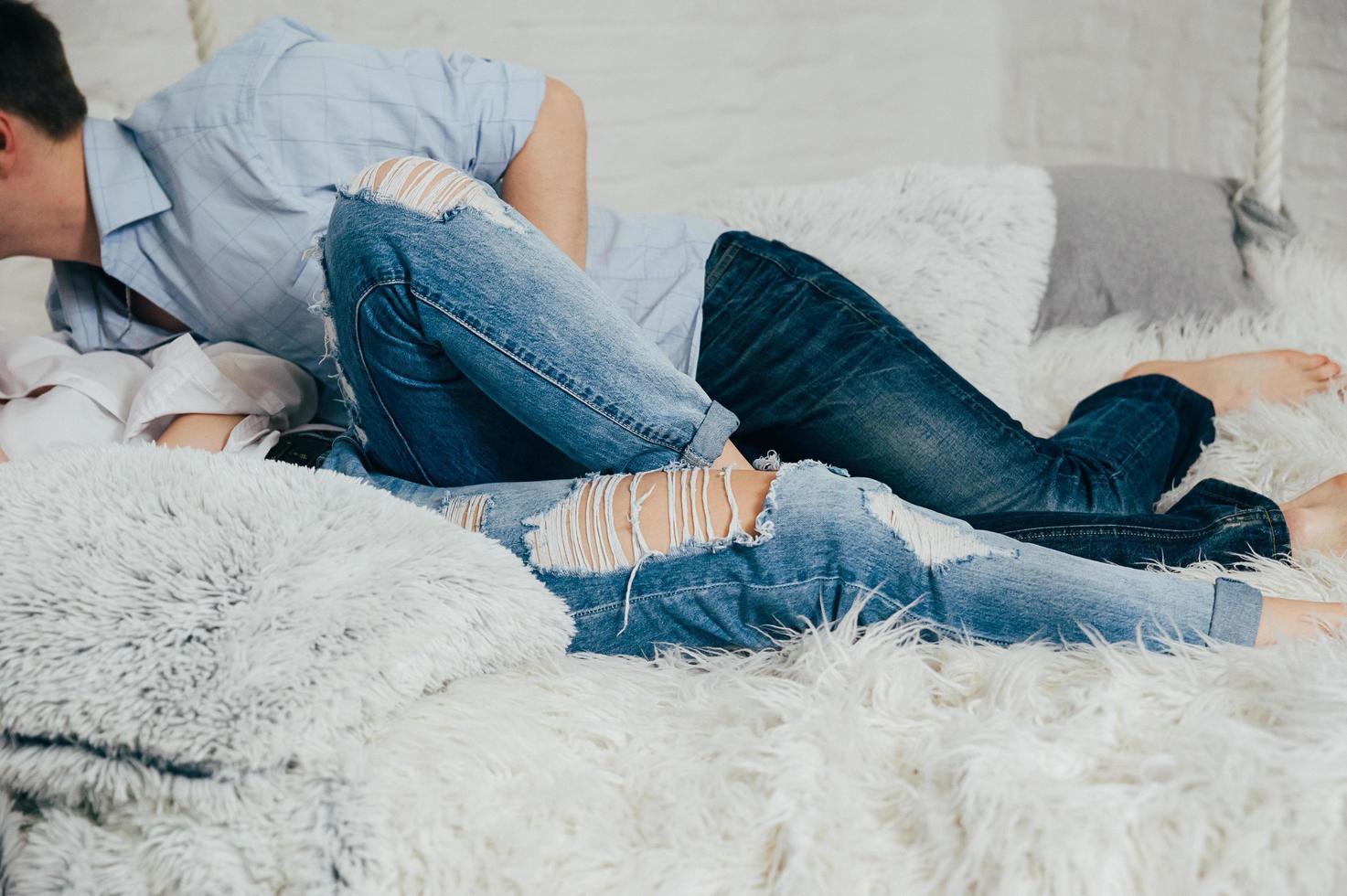 una coppia in jeans e maglietta su un letto sospeso bianco foto