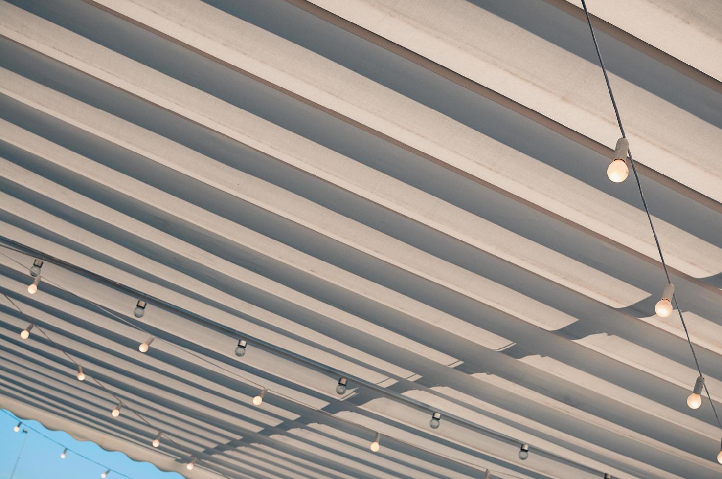 tetto bianco del terrazzo, lampadine appese sotto la tenda da sole foto