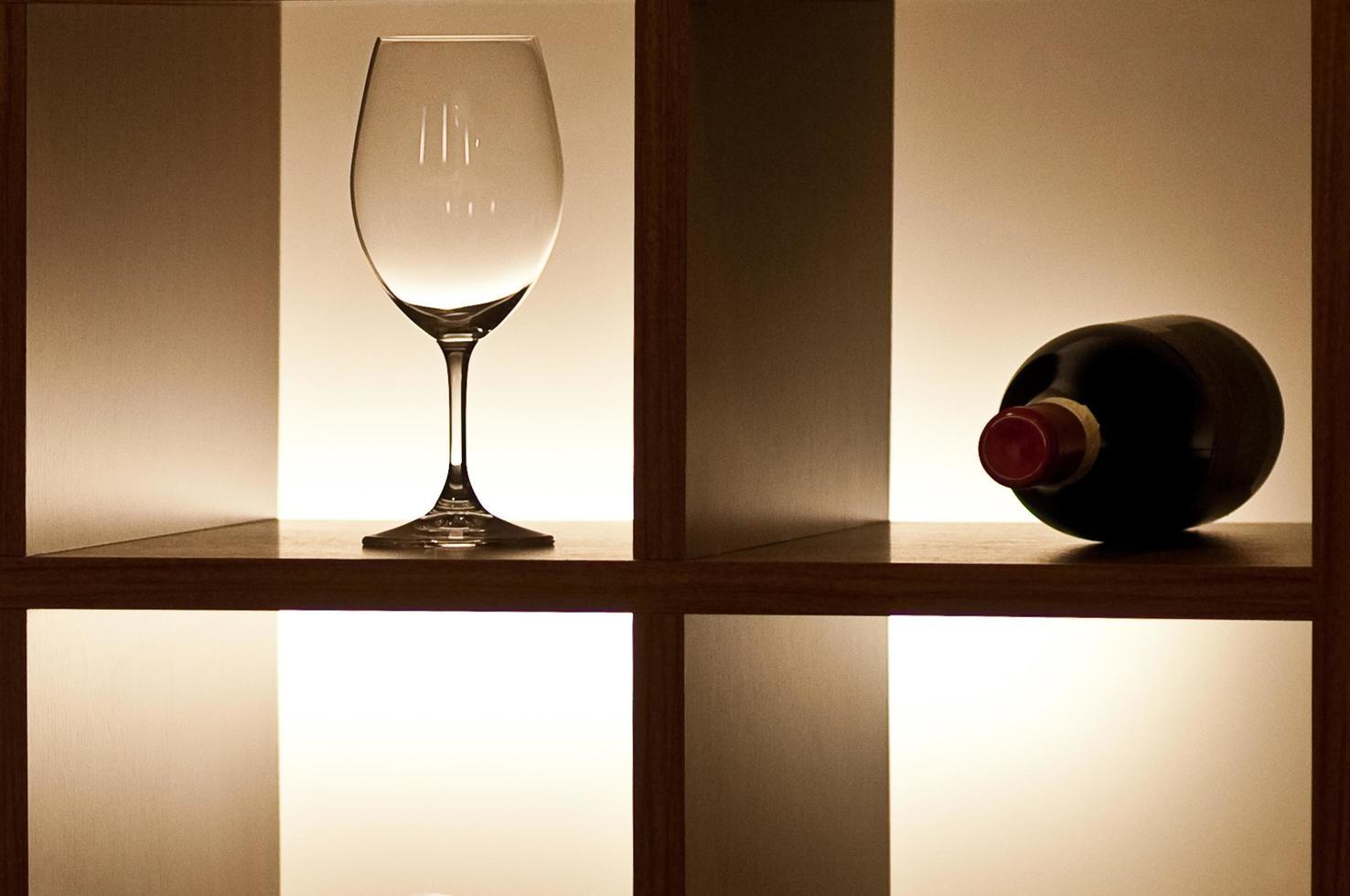 un unico bicchiere di vino vuoto con bellissimi riflessi e una bottiglia chiusa di vino rosso che giace su uno scaffale con illuminazione laterale impostata all'interno foto