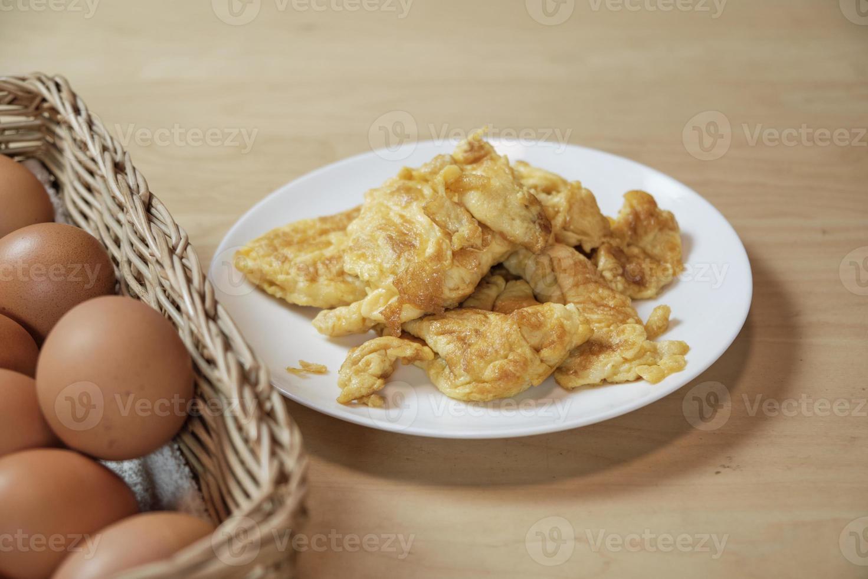 frittate in piatto bianco, cesto di uova sul tavolo in cucina di casa. foto