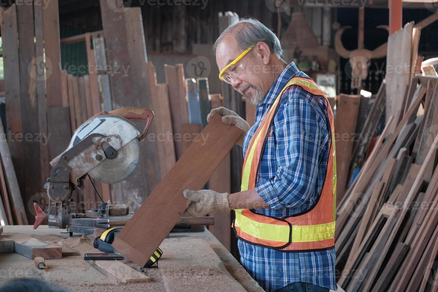 falegname asiatico senior che taglia legname in fabbrica. foto