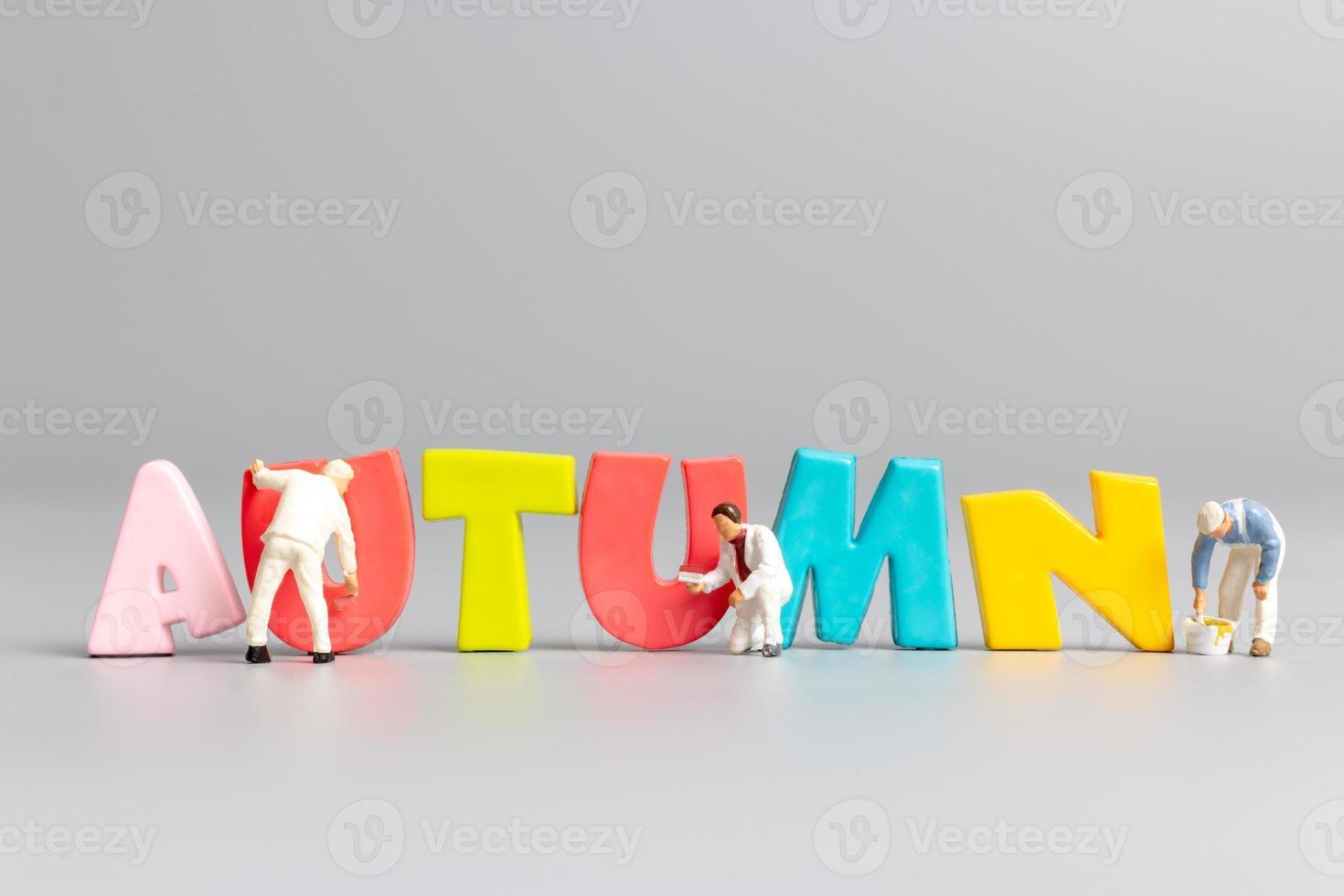 persone in miniatura squadra di lavoratori pittura dell'autunno con posto per il testo foto