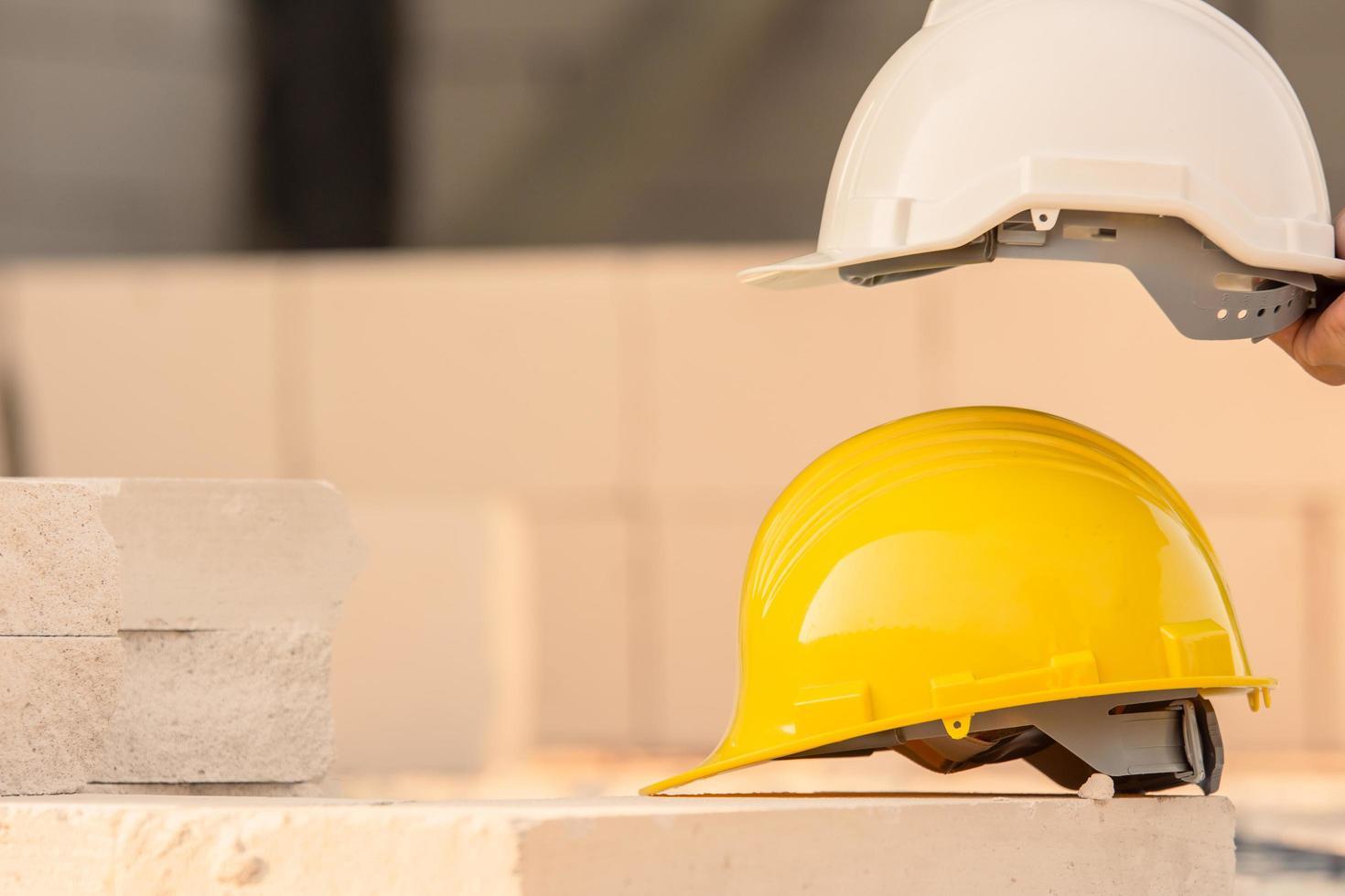 elmetto sullo sfondo della costruzione del sito, sicurezza del casco, festa del lavoro foto