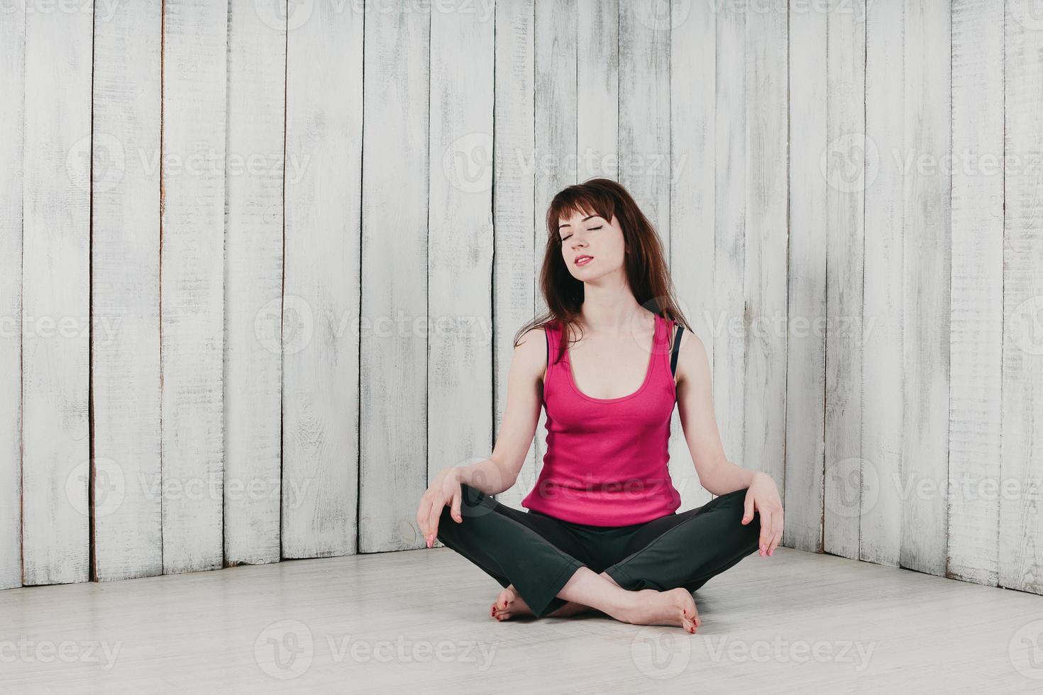 ragazza in top rosa, seduta a gambe incrociate sul pavimento, sorridente foto