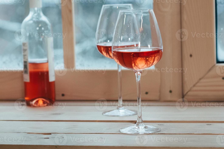 bottiglia di vino rosato e due bicchieri sul davanzale di una finestra foto